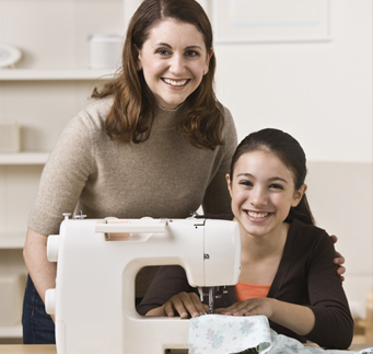Mother and daughter sewing doll clothes together
