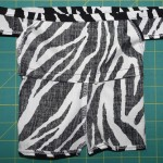 """11. Pull shorts out so that everything is inside out and fold under the ¼"""" (6mm) raw edge that you pressed earlier. Pin in place. This will be the casing for the waist elastic."""