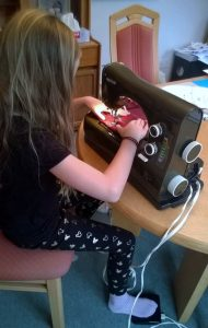Ruth's granddaughter learning how to sew doll clothes