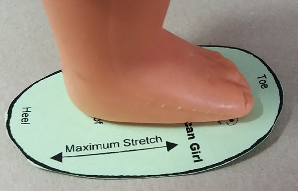 Checking sole size with doll foot
